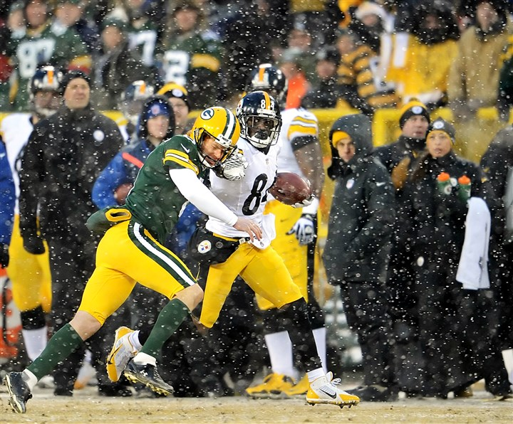 20131222pdSteelersSports06-2 Packers kicker Mason Crosby knocks Steelers' Antonio Brown out of bounds saving a score in the second quarter at Lambeau Field Green Bay Wisconsin.