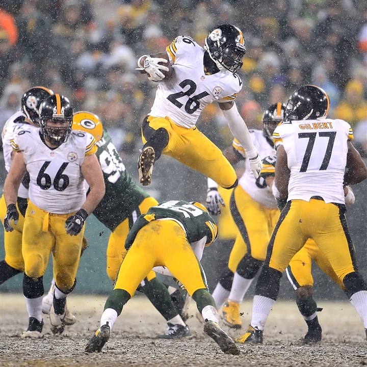 snoter1223 Steelers running back Le'Veon Bell leaps over a defender Sunday at Lambeau Field in Green Bay.