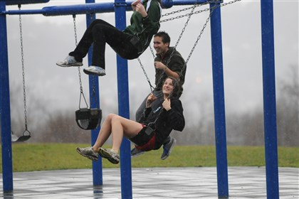 warmsnap1222new From top: Orly Olbum, Eli Boninger, and Gaorlyn Le Garrec, all of Squirrel Hill, enjoy the swings in Schenley Park on an unseasonably warm but wet Saturday afternoon.