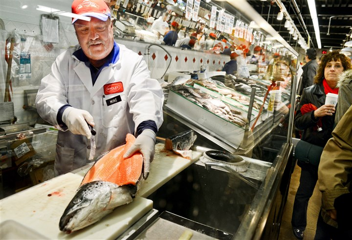 20131223ds7FishesLocal01 Mike Hartman of Lawrenceville, who has been with the business for 33 years, fillets a large salmon as customers shop at Wholey's Fish Market in the Strip District for the Feast of the Seven Fishes tradition on Monday. gone fishing for seven fishes
