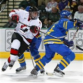 Sidney Crosby (in white) of Team Canada leaps between two players from Team Sweden during the World Jr. Hockey tournament on December 27, 2004 at the Ralph Englestad Arena in Grand Forks, North Dakota.
