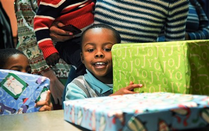 "20131225jrDinnerLocal1 Jeremiah Young, 6, of Turtle Creek smiles as he is handed a present at the ""Christmas Day at Pitt"" Wednesday."