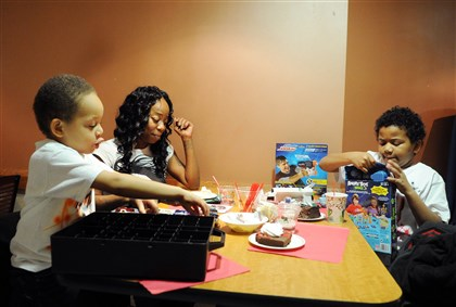 "20131225jrDinnerLocal3 Nicky West of Crafton and her sons Damon Richie III, 5, left, and Damon Richie Jr., 10, open presents during the ""Christmas Day at Pitt"" Wednesday."