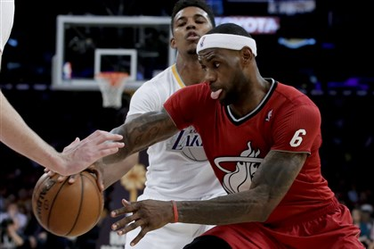 nba1226 Miami Heat forward LeBron James, right, drives past Los Angeles Lakers forward Nick Young in the second half Wednesday.
