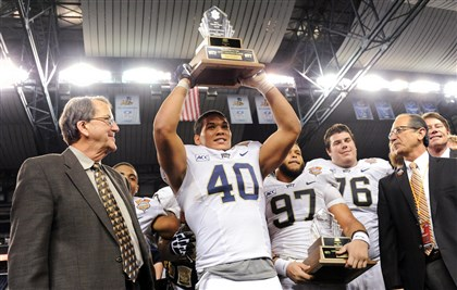 20131226mfpittsports08 Pitt's James Conner lifts the Most Valuable Player award after defeating Bowling Green in the Little Caesars Pizza Bowl at Ford Field in Detroit.
