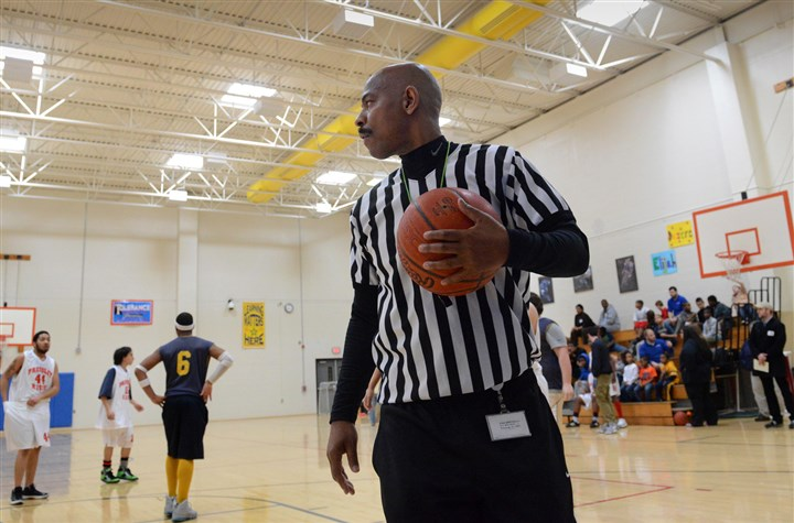 20130307lfPressleyRidgeSpor.8-2 Former Duquesne University standout B.B. Flenory, now a transition specialist at Pressley Ridge, wears his familiar referee stripes and oversees a basketball game at the North Side school in March. Sha'Ron Williams, far left, waits for play to resume.