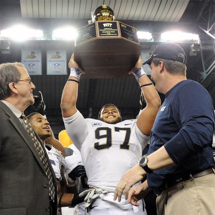Pitt's Aaron Donald Pitt's Aaron Donald holds the championship trophy after defeating Bowling Green in the Little Caesars Pizza Bowl at Ford Field in Detroit Thursday.