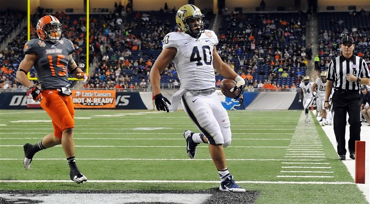 20131226mfpittsports06 Pitt's James Conner runs into the end zone for a touchdown ahead of Bowling Green's Ryland Ward in the first quarter of the Little Caesars Pizza Bowl at Ford Field in Detroit.