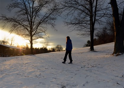 20131218bwSunLocal01 Jackie Kramer of Collier Township, takes a walk as the sun sets near her home in Settler's Cabin Park as dusk approaches.