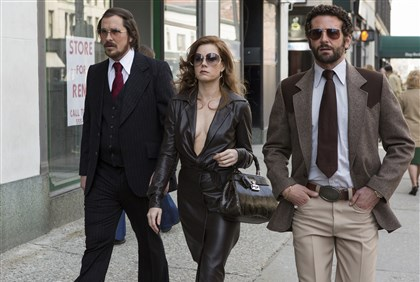 "Fashion-American Hustle Christian Bale, left, as Irving Rosenfeld, Amy Adams as Sydney Prosser, center, and Bradley Cooper as Richie Dimaso walk down Lexington Avenue in a scene from Columbia Pictures' film, ""American Hustle."" Rosenfeld rocks an elaborate comb-over, complete with fuzzy, glue-on hairpiece. Adams' dress is vintage Halston. For accessories, her glasses are vintage Christian Dior, her handbag is Gucci, and shoes are vintage. Bale's suit, tie, shirt, and glasses are vintage. Cooper's suit, tie shirt, belt, and glasses are vintage."