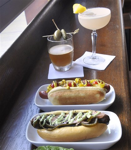 Franktuary  Front to back: the Bangkok, Negishi and Chicago Imposter hot dogs and the Holy Cow drink (top left) and the Flying Nun at Franktuary in Lawrenceville.
