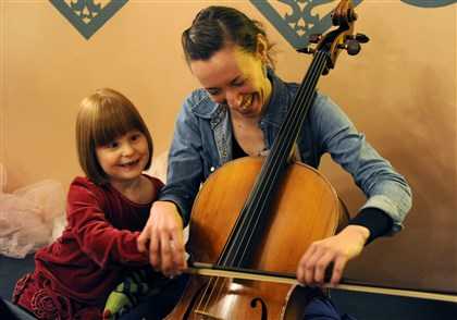 "20131227BalletLocal03-1 Rachel Smith of Firefly Arts teaches Zoey Silinskas, 6, of Ross, who was born premature, how to play a cello Friday before ""The Nutcracker"" at the Benedum Center."