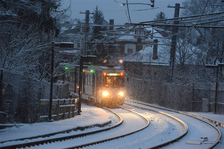 20131126dsSnowLocal02.jpg A light-rail train bound for Downtown makes its way through Dormont as the snow falls during a snowy commute late last month.
