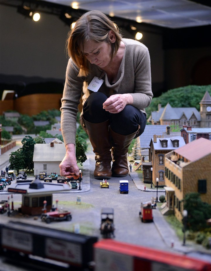 PattyRogers Patty Rogers, historic exhibit curator at the Carnegie Science Center, makes adjustments to model cars on the miniature railroad exhibit.