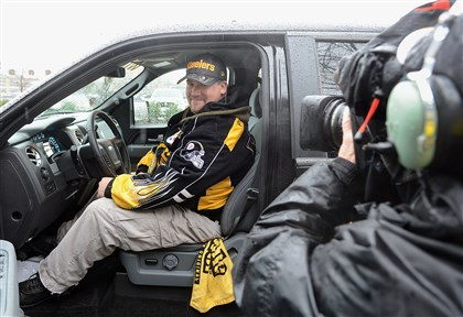 "20131229radFordTruckLocal03-2 Anthony Phillips of Pittsburgh's Beechview neighborhood poses for the cameras after he was awarded the Ford F-150 emblazoned with Steelers decorations in Ford's ""Toughest Team, Toughest Truck"" sweepstakes."
