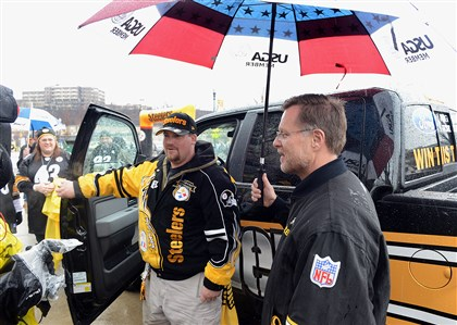 "20131229radFordTruckLocal05-4 Joe Thurby, chairman of the Neighborhood Ford Store, shields contest winner Anthony Phillips of Pittsburgh's Beechview neighborhood for the rain while speaking to reporters after he was awarded the Ford F-150 emblazoned with Steelers decorations in Ford's ""Toughest Team, Toughest Truck"" sweepstakes."
