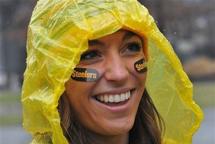 20131229lrwetstandalone04-3 Decked out in Steelers rain gear, Whitney Dartnell, from Hackettstown, N.J., heads for the T station at Gateway Center en route to Sunday's Steelers-Browns game at Heinz Field.