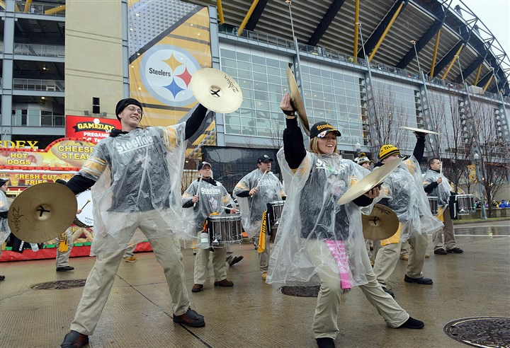 20131229radWetTailgateLocal03-7 The Pittsburgh Steeline drumline serenades fans Sunday outside Heinz Field in the rain before the Steelers-Browns game.