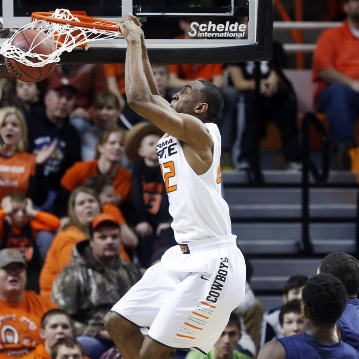 rmu1231c-2 Oklahoma State forward Markel Brown dunks against Robert Morris.