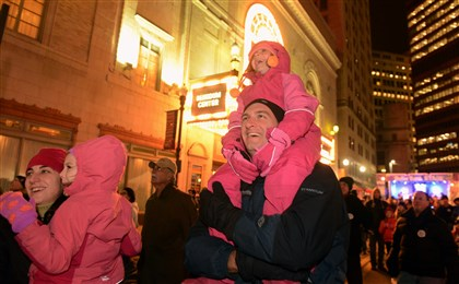 20131231bwFirstLocal08 First Night has Stephanie Myers holding daughter Elizabeth,4, while husband Keith holds their daughter, Grace,6, all of Upper St. Clair, as they watch the early fireworks in front of the Benedum Center in Downtown Pittsburgh.
