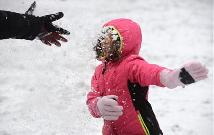 20131231CountdownLocal02-1 Keturah Wolfgramm, 4, of Anaheim, Calif., gets a face full of snow Tuesday thrown by her father, Phil Wolfgramm, outside the Allegheny Commons on the North Side. They are visiting family over the holidays and it is her first time seeing and playing in snow.