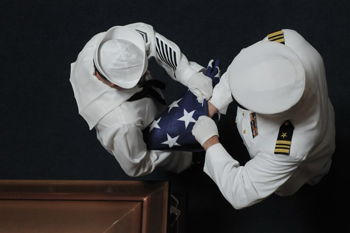 20140103_may.jpg Boatswain's Mate 1 Raymond Monath, left, and Lt. Cmdr. Jeffrey Hawn fold an American flag for presentation to the family at the funeral of Navy veteran James Simmons Sr. in early May at Forest Lawn Gardens Cemetery in Peters.