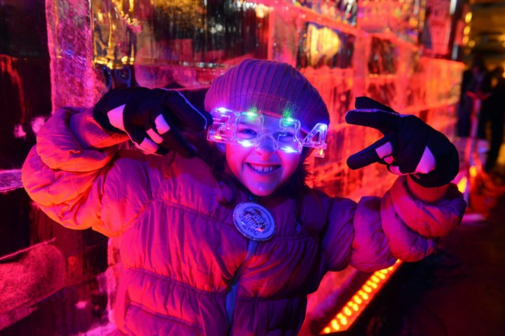 20131231bwFirstLocal07 Channing Brook, 8, of Forest Hills poses with her 2014 glasses in front of the ice labyrinth made by Ice Creations' Rich Bubin for First Night in Downtown Pittsburgh.