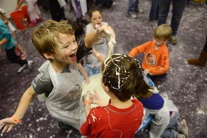 "20140101MWHmessLocal01 Max Thomas, left, 6, of Moon puts ""ooblek,"" a gooey substance made by mixing water and corn starch, into the hair of Alex Repinski, 5, of Wexford during the annual Mess Fess on Wednesday at the Carnegie Science Center."