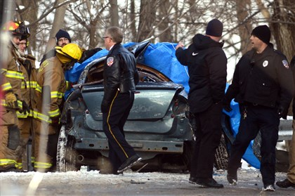 20140103dsFatalLocal02-1 Officials work at the scene of a crash between a school bus and a sedan on Tarentum Bridge Road/Route 366, near the intersection of Marlboro Road, in New Kensington. The driver of the car was killed; no students were hurt.