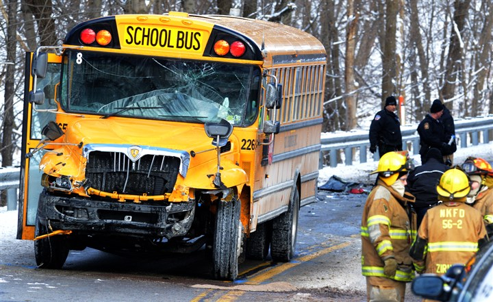 20140104dsFatalLocal04-3 Officials work at the scene of a crash between a school bus and a sedan on Tarentum Bridge Road/Route 366, near the intersection of Marlboro Road, in New Kensington. The driver of the car was killed; no students were hurt.