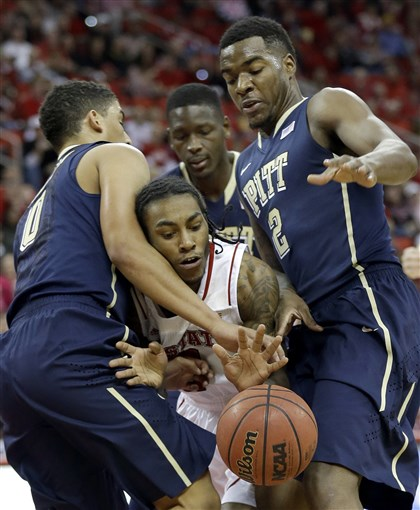 pitt0105c-2 James Robinson, left, and Michael Young, right, guard North Carolina State's Anthony Barber, center, vie for the ball during the first half in Raleigh, N.C., Saturday.