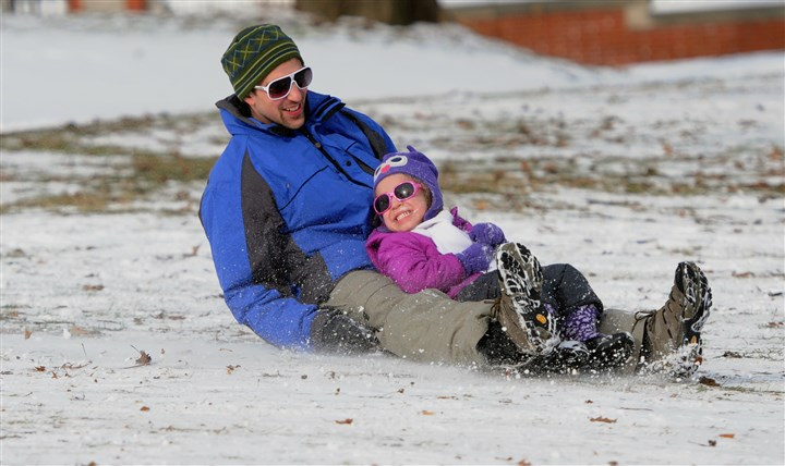 20140104 Sledding  Four-year-old Sadie DeLuca of Friendship is all smiles with her father Joe while spinning to a stop during her first time sledding in Mellon Park on Saturday.
