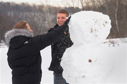 20140105lrsnowmanstandalone02-10 Tom Sporrer, a law student at Pitt, helps fellow law student Katie Cianciolo brush the dirt , leaves and grass from their snowman Sunday in North Park. The two students spent Saturday at Frick Park and decided to try somewhere different on Sunday.
