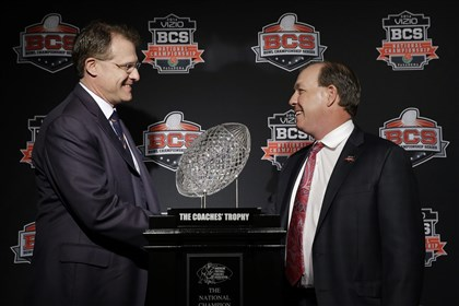 BCS Championship Football Auburn head coach Gus Malzahn, left, and Florida State head coach Jimbo Fisher shake hands in front of The Coaches' Trophy during a news conference Sunday for the BCS National Championship in Newport Beach, Calif. Florida State plays Auburn today.