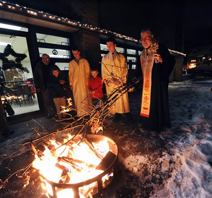 "20140114JHLocalYule04 The Very Rev. Stevan Rocknage, pastor of St. Sava Serbian Orthodox Church in McKeesport, right, oversees the annual burning of the yule log, or ""badnjak,"" on Monday evening at the church on Hartman Street. The entire ceremony is usually held outdoors, but due to extreme cold weather, the Orthodox Christmas Eve service was held in the parish hall and only the burning of the log was outside."