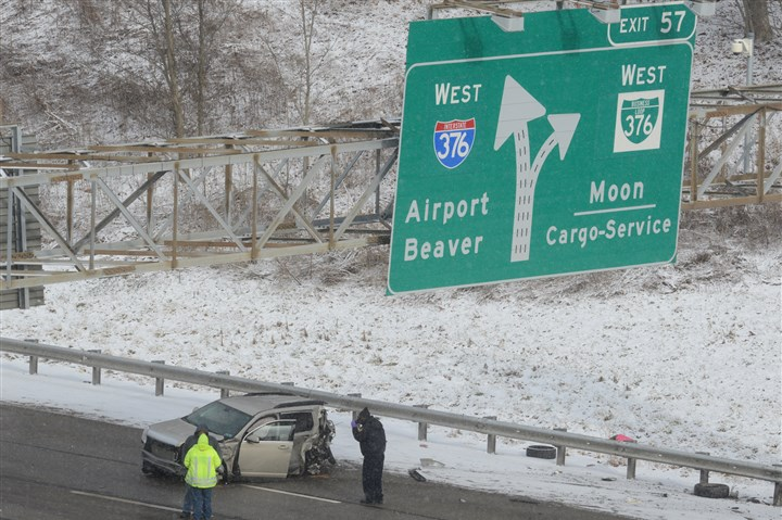 20140106dsFatalLocal04-3 A badly damaged car can be seen Monday on the Parkway West after a fatal accident. A man died and a woman was injured when a tractor-trailer and an SUV collided on the outbound side near Montour Run Road in Moon.