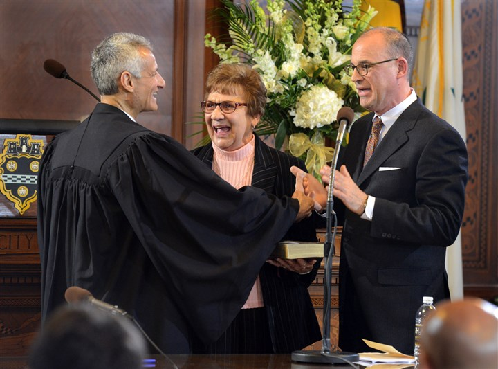 Bruce Kraus council president swearing in Judge Gene Riccardi congratulates Bruce Kraus after swearing him in as the new president of Pittsburgh City Council on Monday. Mr. Kraus's mother, Deloris, held the Bible for her son.