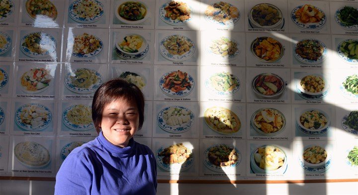 20140103bwKaMeiMag01  Ka Mei restaurant owner Carol Cheng in front of the wall of dishes they serve.