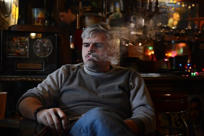 Cigar smoking Robert Baugh of Troy Hill smokes a cigar with friends Wednesday afternoon at Leaf & Bean in the Strip District.