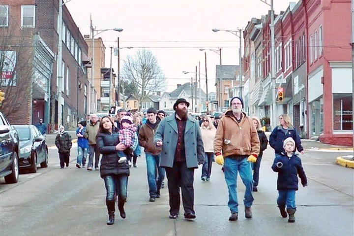 20140106jeanetteD Jeannette resident Chad Fetty, center with beard, leads a crowd of more than 100 people on Sunday as they march through the city as part of an anti-violence/peace rally.