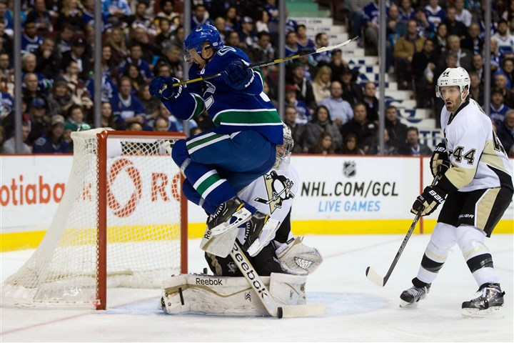Penguins Canucks Fleury makes save The Canucks' Henrik Sedin, left, jumps as Penguins goalie Marc-Andre Fleury, center, makes the save while Brooks Orpik, right, watches during the first period.