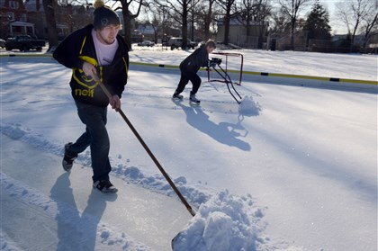 20140109dsIceTimeLocal Brandon Price and Marcus Moroney, both of Verona, work on shoveling off a layer of snow in order to play some hockey. The snow had accumulated on a temporary ice rink at Riverside Park in Oakmont.