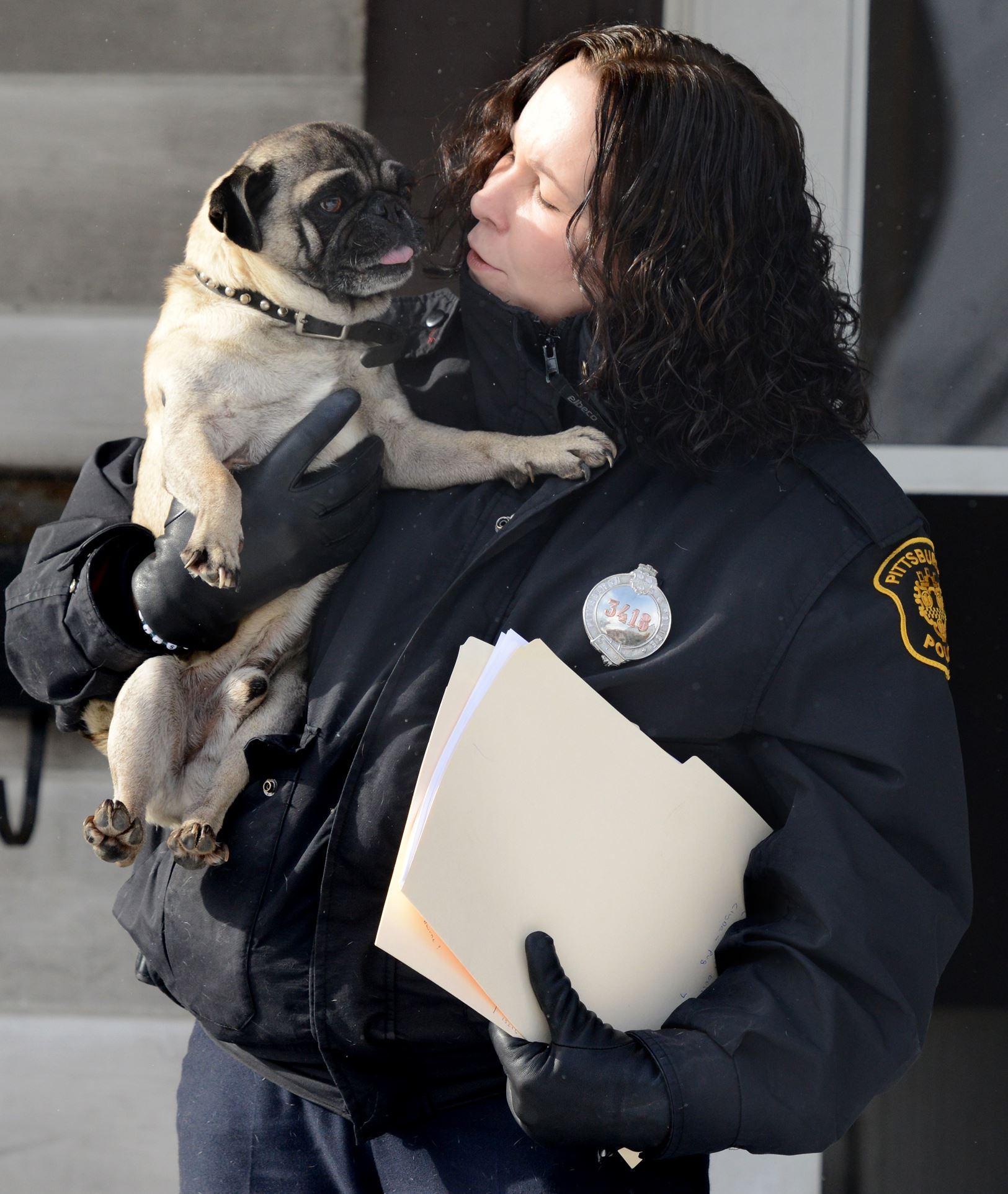 Police officer and dog Pittsburgh police officer Christine Luffey holds an 8-year-old pug in Allentown Tuesday after checking on him during cold weather.