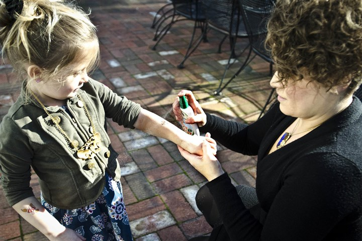 20140102SMALLBIZ-BUGS1 Jayme Bella, CEO of Greener Days L.L.C., right, uses Greenerways Organic Bug Spray on her daughter, Andrea, last month in Langhorne, Pa. The firm had its origin in bug troubles she had in her North Jersey home after a nor'easter in 2008.