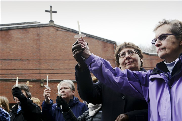 20140110 Prayer vigil for Aliquippa nun Sister Karen Stoila, left, and Sister Sue Ann Orange of the Sisters of St. Joseph of Baden hold up a candle in unity during a rally at St. Titus Church in Aliquippa on Friday.