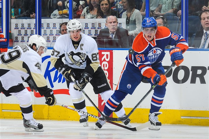 20140111penguins4-1 David Perron of the Edmonton Oilers chases a loose puck against Brian Gibbons and Sidney Crosby