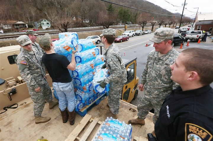 Chemical Spill  Members of the West Virginia Army National Guard, along with a member of the Belle Police Department and a volunteer, transfer emergency water from a military truck to a forklift as people line up for water.