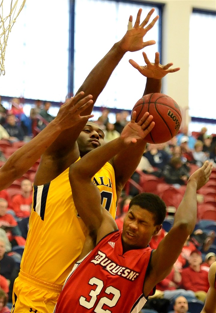 20140112pdDuquesneSports04-3 La Salle's Jermaine Davis blocks a shot by Duquesne's Desmond Ridenour in the second half Sunday at A.J. Palumbo Center.