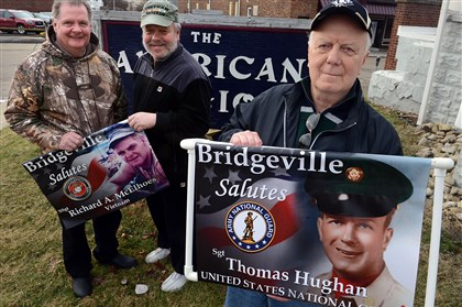 Bridgeville Veterans Posters Veteran Thomas Hughan Jr. with the poster depicting him in the Army that will be hung with other veterans on Bridgeville business district utility poles. Rick McElhoes, left, and Joe Solomon are from American Legion Post 54.