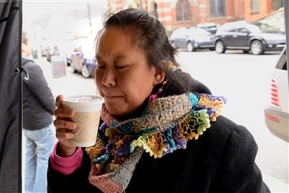 Woman drinks Mexican hot chocolate Alex Jones of Mt. Lebanon savors a cup of Mexican hot chocolate at a stand in the Strip District.